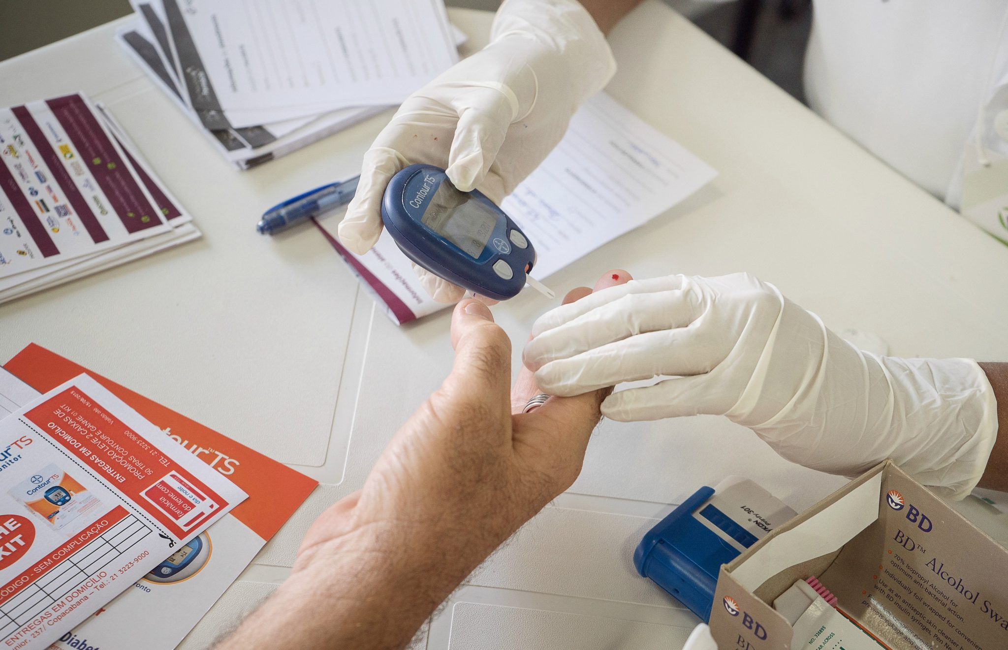 Pessoa realizando teste de diabetes em paciente